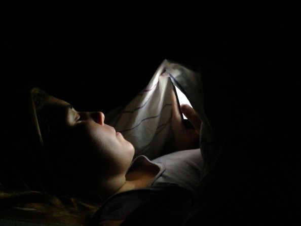 A woman browsing the internet and using her smartphone in the middle of the night under the covers to not disturb her husband.